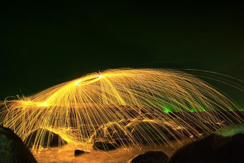 Chispas de oro calientes que vuelan de las lanas de acero ardientes de giro del hombre en una esfera en Rocky Shoreline fotografía de archivo