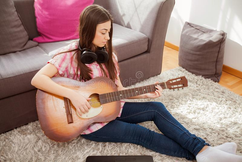 chitarra acustica del gioco della giovane donna immagine stock