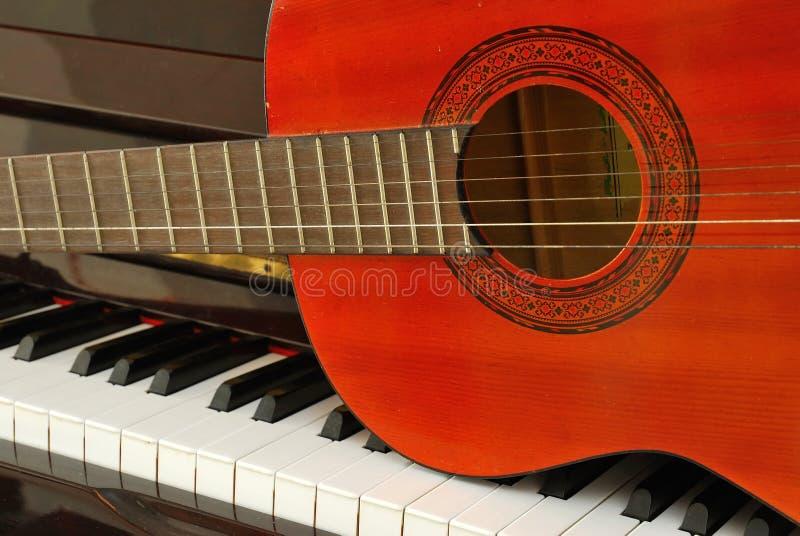 Chitarra acustica sulla tastiera di piano fotografia stock