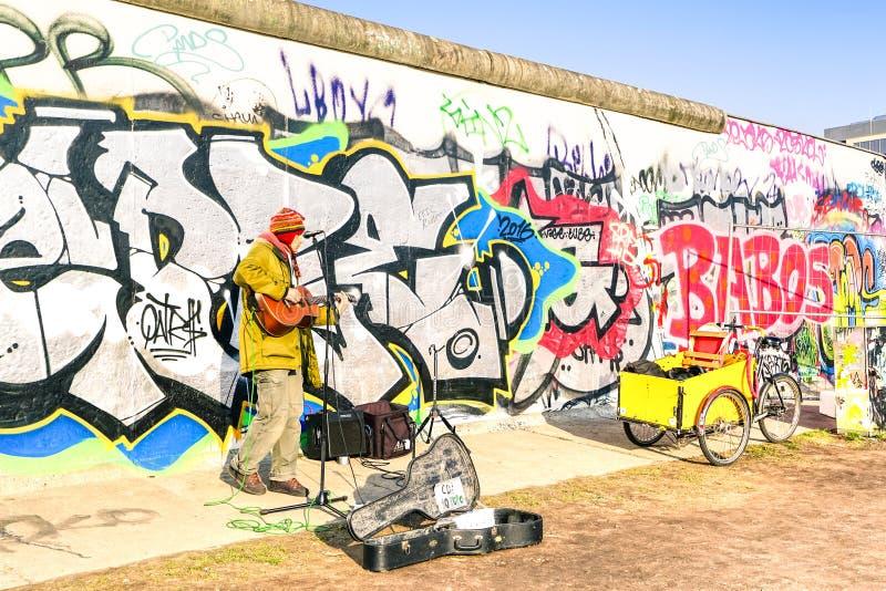 Chitarra d'esecuzione dell'artista della via alla galleria del lato est a Berlino immagini stock