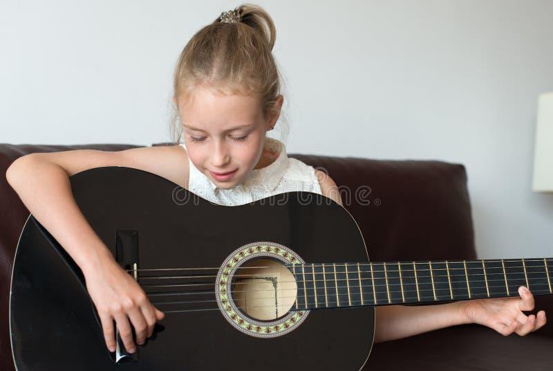 Chitarra del gioco della ragazza immagini stock