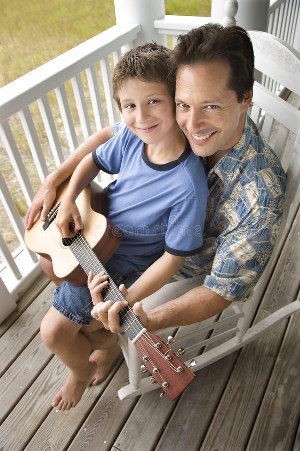 chitarra del padre che gioca il figlio del portico immagine stock