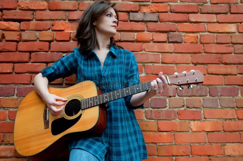Chitarra di gioco femminile del giovane Brunette fotografia stock