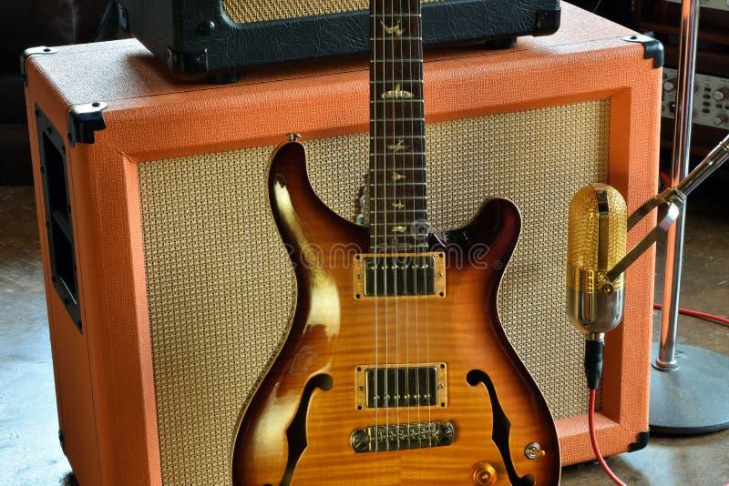Chitarra elettrica d'annata di Hollowbody dei semi con la foto delle azione dello studio dell'amplificatore e del microfono a nas immagini stock libere da diritti