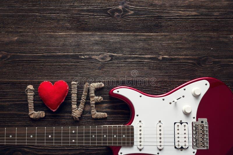 Chitarra elettrica rossa con l'amore di parola e cuore su un woode scuro immagine stock
