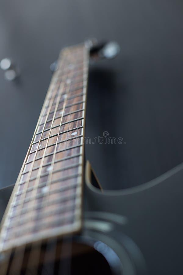 Chitarra nera su fondo nero immagini stock