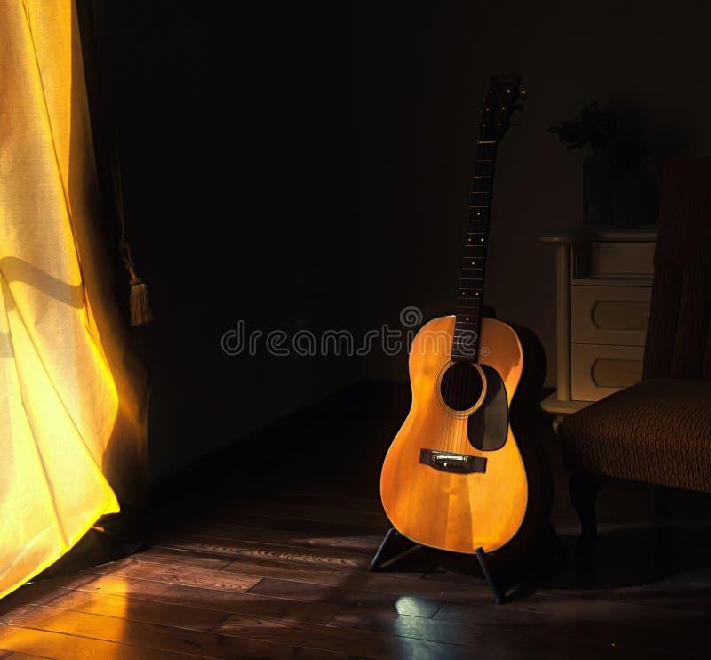 Chitarra spagnola acustica su un supporto nelle ombre lunatiche di una stanza scura con luce intensa che entra da dietro una tend fotografia stock libera da diritti