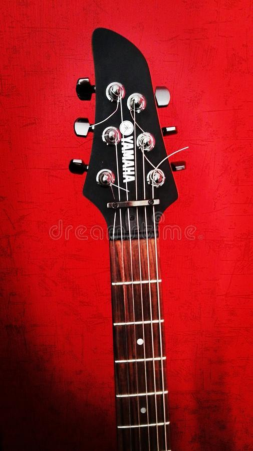 Chitarra su fondo rosso fotografia stock