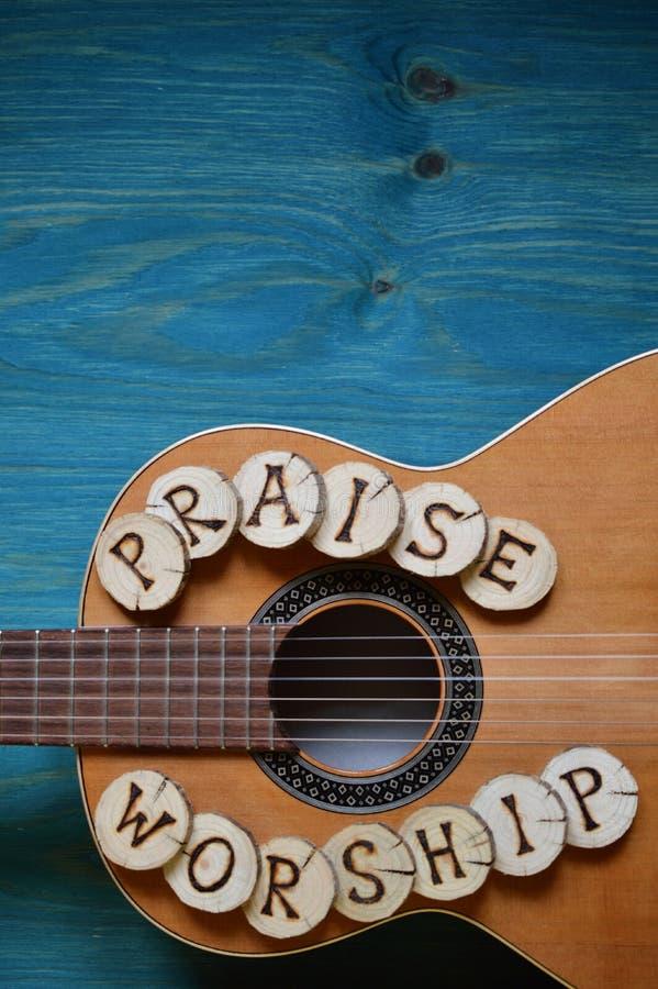 Chitarra su legno con le parole: ELOGIO e CULTO immagini stock libere da diritti