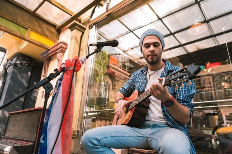 Chitarrista maschio bello che gode della musica sulla chitarra fotografie stock libere da diritti