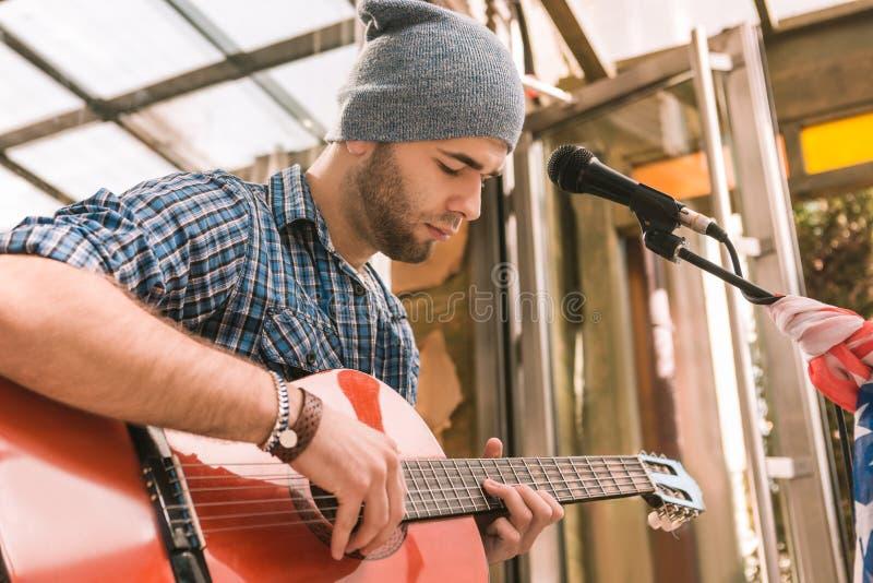 Chitarrista maschio messo a fuoco che padroneggia la sua tecnica della chitarra fotografia stock