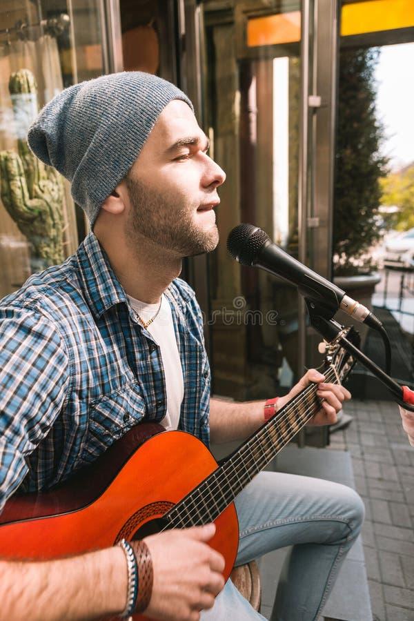 Chitarrista maschio messo a fuoco che si concentra sulla canzone vicino alla barra fotografia stock libera da diritti