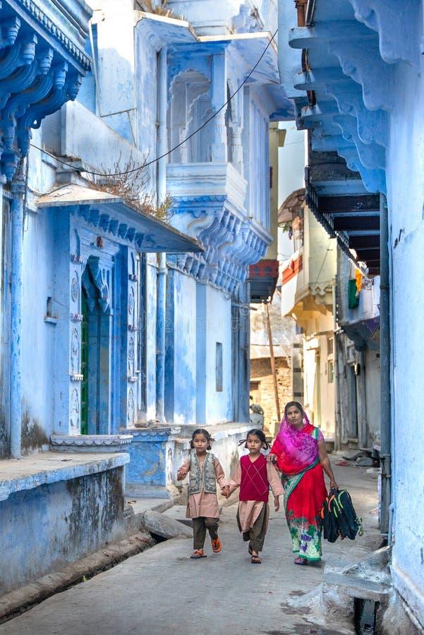 Chittorgarh/India-25 02 2019: De vrouwen met haar jonge geitjes gaat naar school stock afbeeldingen