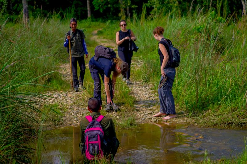 CHITWAN, NEPAL - NOVEMBER 03, 2017: Some tourists crossing without shoes a creek in Chitwan National Park.  royalty free stock photo