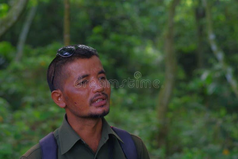 CHITWAN, NEPAL - 3 NOVEMBRE 2017: Ritratto di una guida turistica che parla al turista dei pericoli dentro del fotografia stock