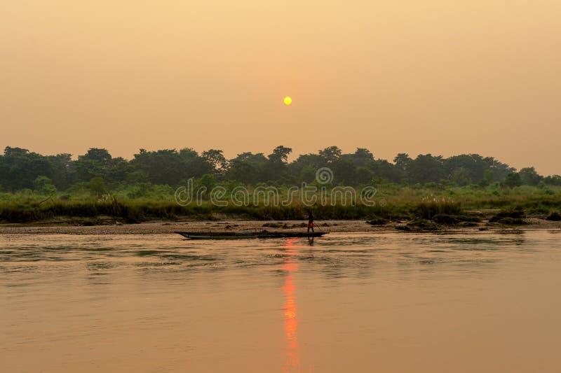 CHITWAN, NEPAL - OKTOBER 27, 2013: Punter drijfroeiboot op wilde rivier dramatische zonsondergang in het Nationale Park Nepal van royalty-vrije stock foto's
