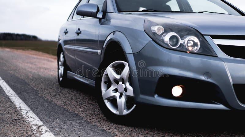 Chiuda aperto di nuova automobile d'argento che parcheggia sulla strada fotografie stock libere da diritti