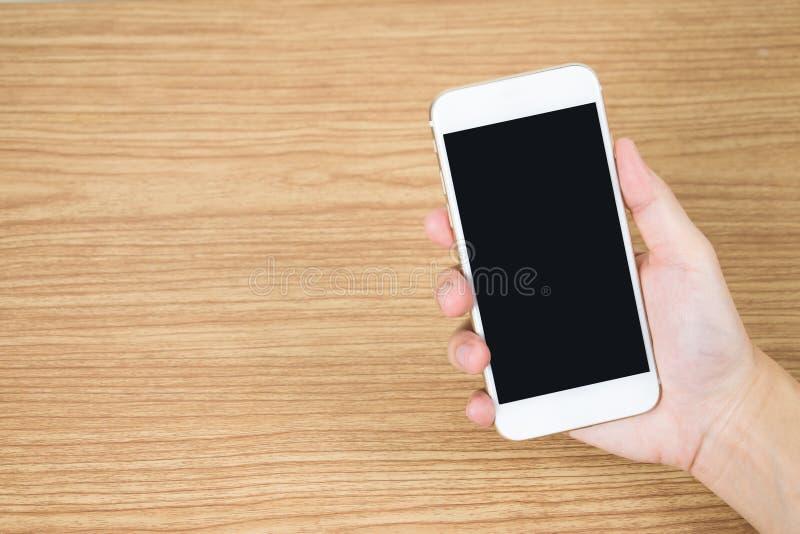Chiuda fino alla mano che tiene il cellulare sulla vecchia tavola di legno nella stanza fotografia stock