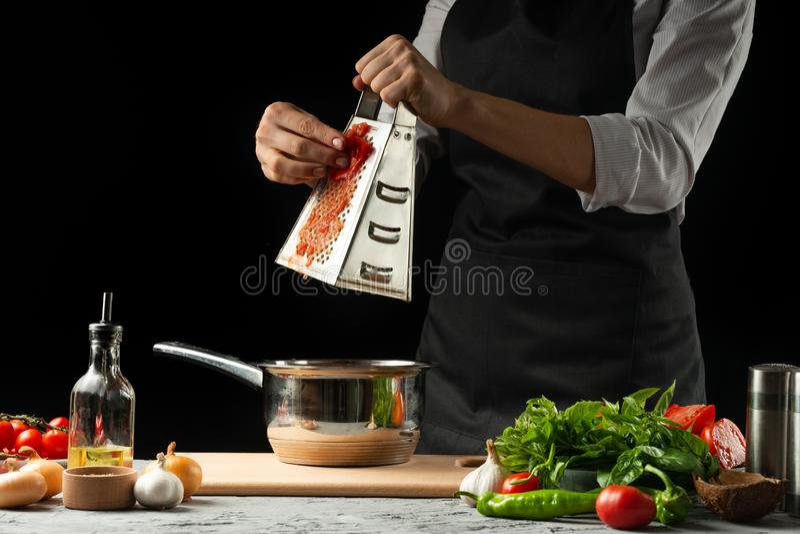 Chiuda il chef& x27; mani di s, preparanti una salsa al pomodoro italiana per i maccheroni Pizza Il concetto della ricetta di cot immagine stock libera da diritti