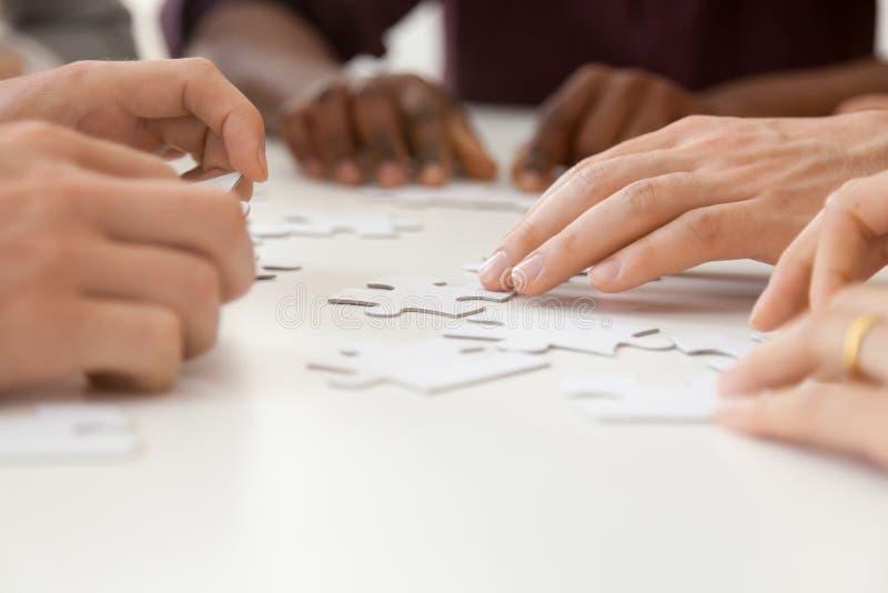 Chiuda insieme su del puzzle di montaggio del diverso gruppo del lavoro immagine stock libera da diritti
