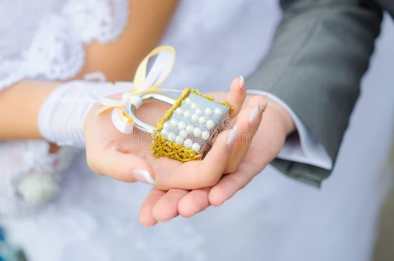 Chiuda nelle mani delle persone appena sposate fotografie stock