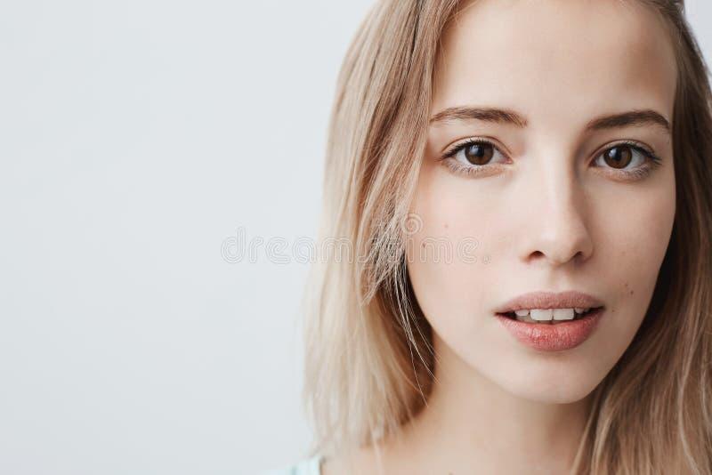 Chiuda pensively sul ritratto di femmina europea abbastanza bella con pelle sana pura, sguardi alla macchina fotografica con legg immagine stock