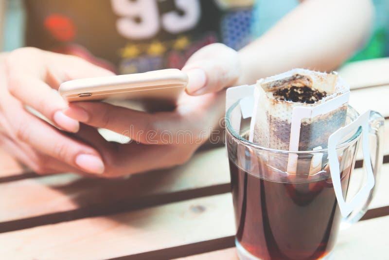 Chiuda su caffè americano con la donna che per mezzo dello smartphone, lo stile di vita, Onl fotografie stock libere da diritti