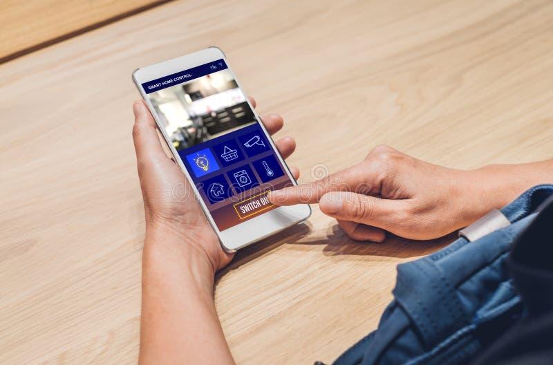 Chiuda su controllo domestico astuto app di uso della mano sul commutatore del telefono cellulare immagini stock libere da diritti