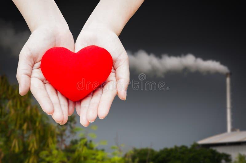 Chiuda su cuore rosso in mani della donna, isolate sul fondo del paesaggio di energia dell'industria, salute, medicina immagini stock libere da diritti