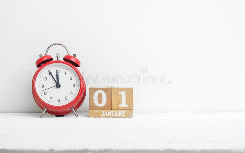 Chiuda su data di calendario del 1° gennaio di legno con la sveglia rossa fotografie stock