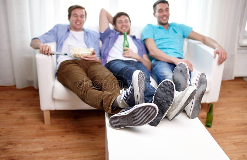 Chiuda su degli amici maschii che guardano la TV a casa fotografie stock
