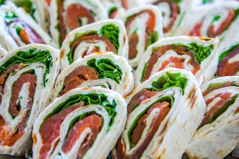 Chiuda su degli aperitivi dei morsi dell'involucro di prosciutto di Parma & di una lattuga immagini stock libere da diritti