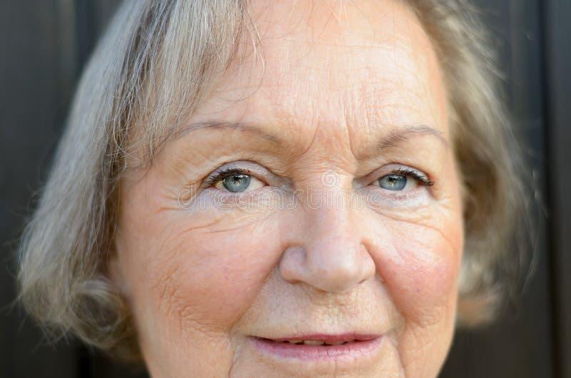 Chiuda su degli occhi azzurri di una signora anziana immagine stock