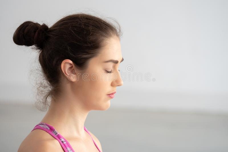 Chiuda su degli occhi chiusi della giovane donna caucasica attraente che fanno meditare con la consapevolezza fotografia stock libera da diritti