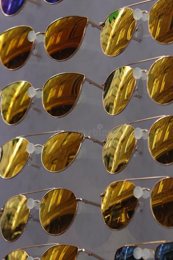 Chiuda su degli occhiali da sole gialli multipli con le riflessioni delle costruzioni storiche di Galata, Costantinopoli fotografie stock
