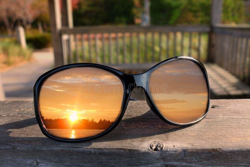 Chiuda su degli occhiali da sole neri brillanti sull'inferriata del gazebo con il tramonto che riflette in lenti fotografia stock libera da diritti