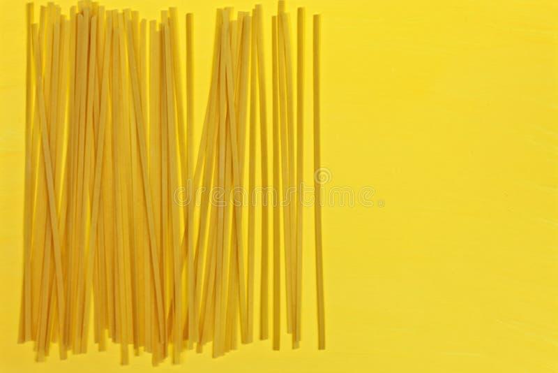 Chiuda su degli spaghetti italiani asciutti crudi della pasta su fondo giallo luminoso Fucilazione con il colore audace fotografia stock libera da diritti