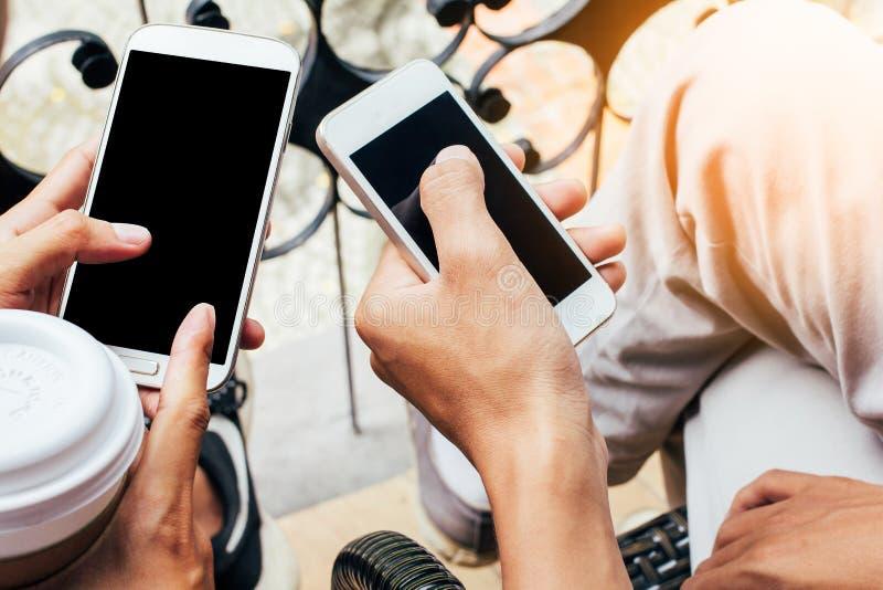 Chiuda su degli uomini e delle mani della donna che tengono il telefono cellulare commovente con lo spazio in bianco della copia  fotografia stock