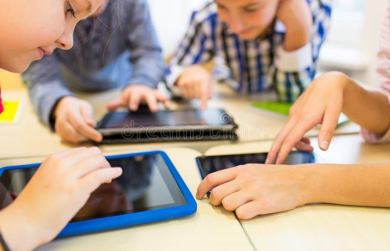 Chiuda su dei bambini della scuola che giocano con il pc della compressa fotografia stock libera da diritti