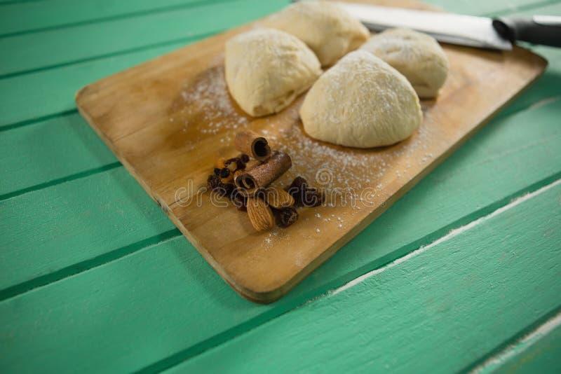 Chiuda su dei biscotti crudi dal coltello sul tagliere immagine stock