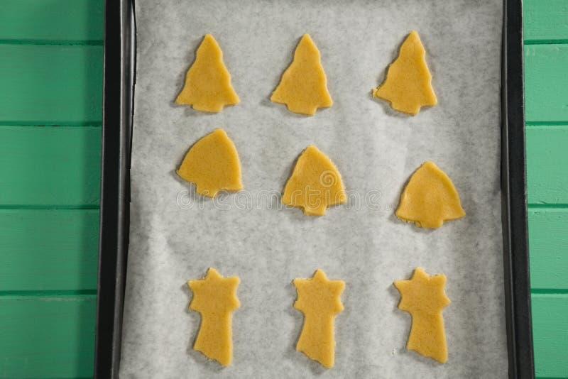 Chiuda su dei biscotti crudi di varia forma in vassoio di cottura fotografia stock libera da diritti