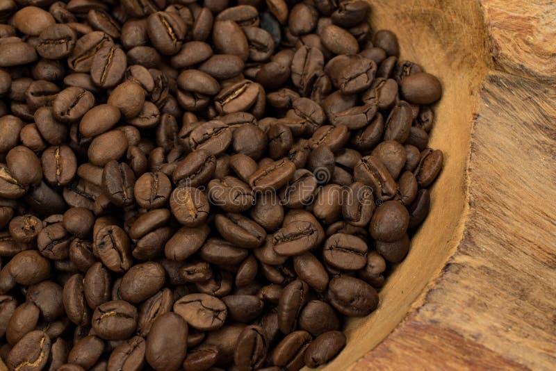 Chiuda su dei chicchi di caffè arrostiti in vecchio legno rustico immagine stock libera da diritti