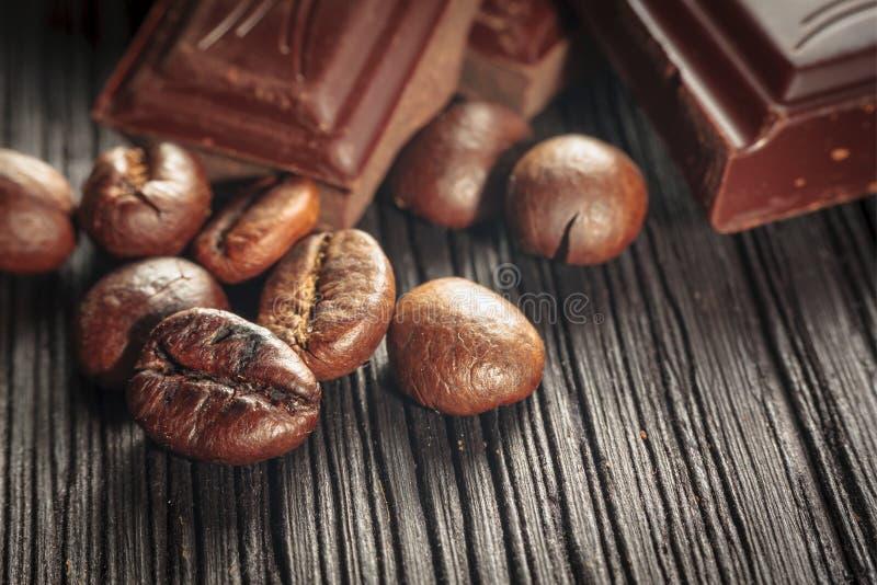 Chiuda su dei chicchi di caffè e del cioccolato immagini stock libere da diritti