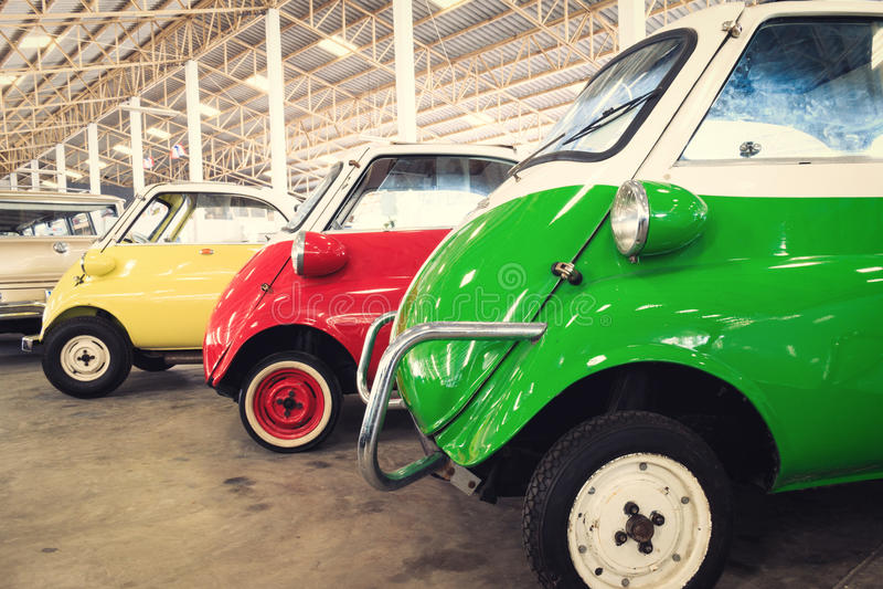 Chiuda su dei dettagli laterali di un'automobile d'annata rossa e gialla di verde, immagine stock