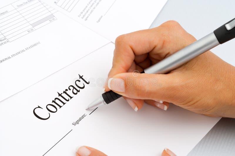 Chiuda in su dei documenti di sign del contratto della mano. fotografia stock