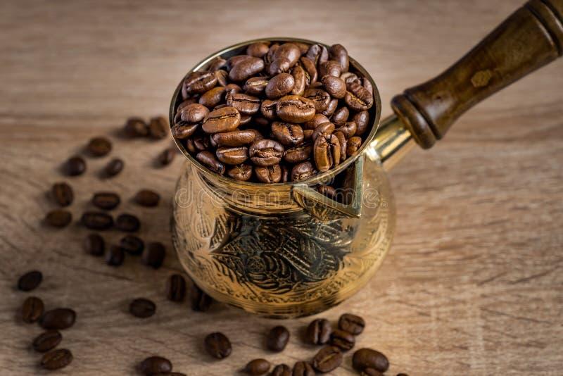 Chiuda su dei fagioli arrostiti freschi del coffe in caffettiera turca tradizionale del cezve sulla tavola di legno fotografie stock