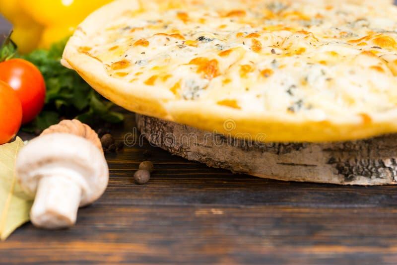 Chiuda su dei formaggi della pizza quattro sul supporto di legno sotto forma di He immagine stock libera da diritti
