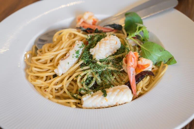 Chiuda su dei frutti di mare piccanti degli spaghetti in piatto bianco fotografie stock