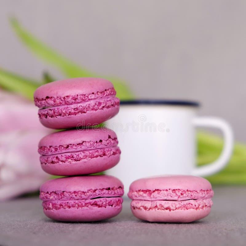 Chiuda su dei macarons francesi dolci, tazza di tè o caffè e fiori della molla su fondo grigio fotografia stock libera da diritti