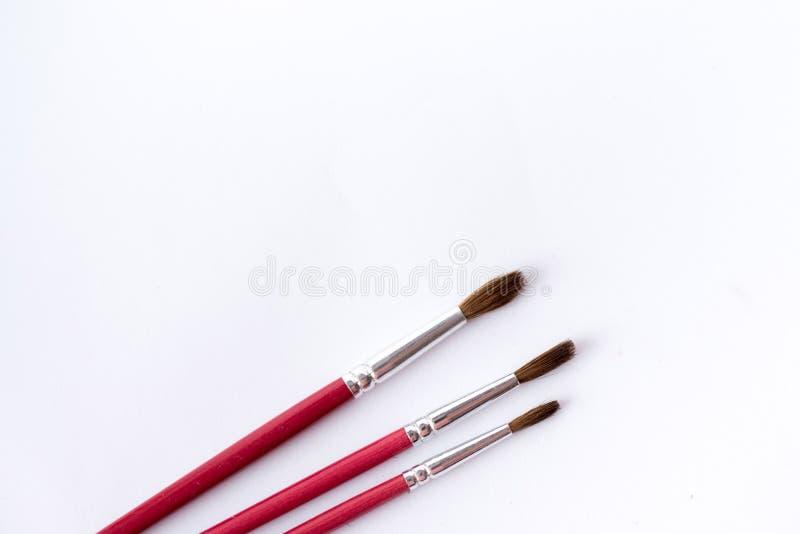 Chiuda su dei pennelli isolati su fondo bianco tavola per pittura testo fotografie stock libere da diritti